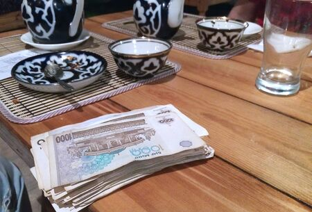 on a wooden table a tea set with a traditional ornament and a large bundle of sums money (the currency of Uzbekistan), focus on money