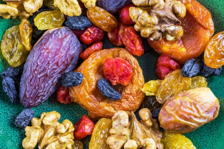 Multi-colored dried fruits and walnuts on a green background, top view, close-up