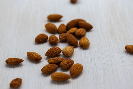 Almond nuts on a white wooden background, side view from above