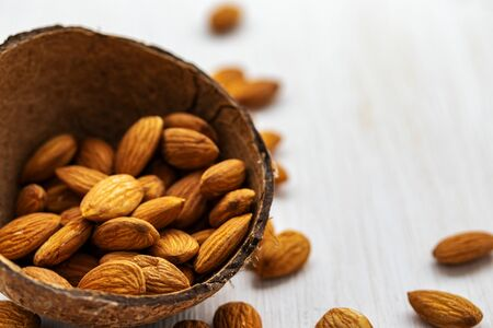 Almond nuts in half coconut shell on white wooden background, side view from above