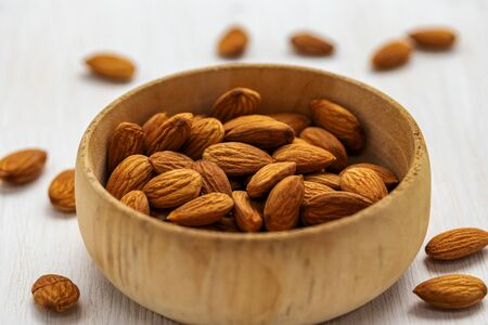Almond nuts in a wide wooden bowl on a white wooden background, side view from above