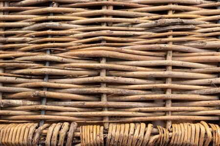 Horizontally intertwined brown willow rods with small vertically intertwined rods at the bottom.