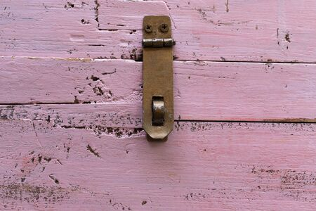 Background in the form of an iron canopy for a lock on an old pink wooden chest