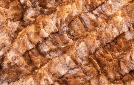 Background in the form of stitched pieces of natural fur light brown color with diagonal stripes