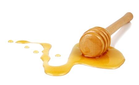 miel que fluye hacia abajo de un palo de madera aislado sobre fondo blanco