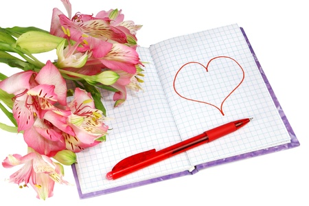 notebook with a pen by flowers and heart isolated on white background photo