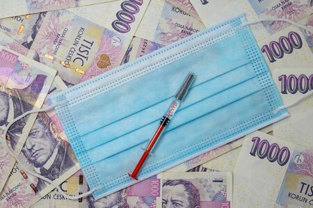 Medical mask laid on Czech money. Syringes are placed on the veil. The label