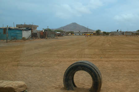 Desert landscape with dwelling and tire. Banco de Imagens
