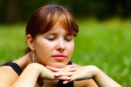 Portrait of a young woman sits on a green meadow in the sun, outdoor in a small city Saarlouis, Saarland   Germany Stock Photo - 14178994
