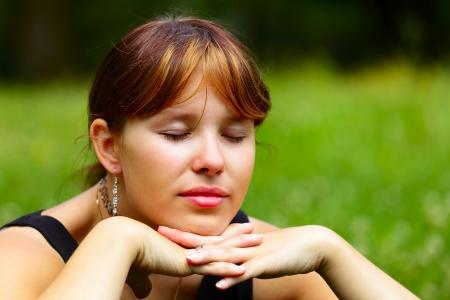 saarlouis: Retrato de una mujer joven se sienta en un prado verde en el sol, al aire libre en una peque�a ciudad de Saarlouis, Saarland Alemania Foto de archivo