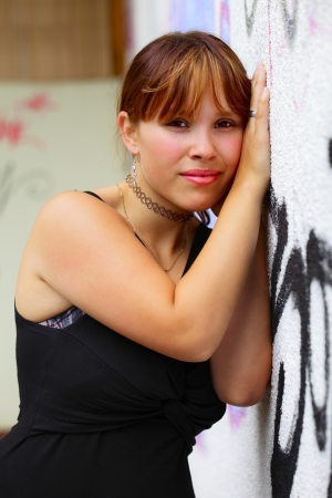 saarlouis: Portrait of a young woman in the background a white  wall with graffiti,  in small city Saarlouis, Saarland   Germany