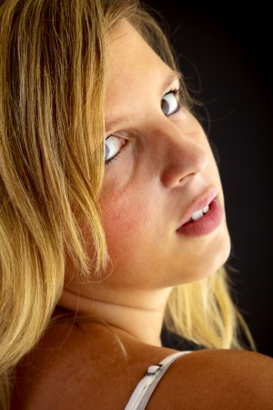 Young blond woman on black background photo