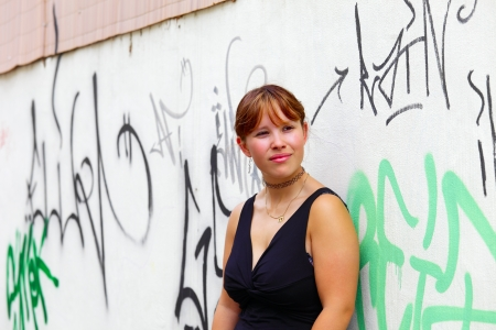 saarlouis: Retrato de una mujer joven en el fondo una pared blanca con el graffiti, en la peque�a ciudad de Saarlouis, Saarland  Alemania