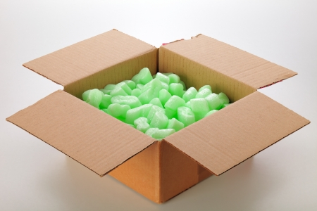 A cardboard box with green packing styrofoam peanuts