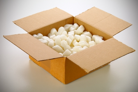 A cardboard box with yellow packing styrofoam peanuts, isolated on white background.