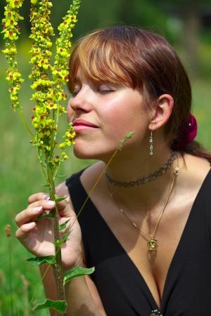 saarlouis: Una mujer joven se sienta en un prado verde en el sol y el olor de una flor silvestre, al aire libre en el parque en una peque�a ciudad de Saarlouis, Saarland  Alemania Foto de archivo