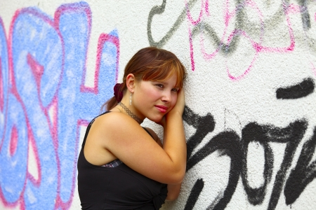 saarlouis: Portrait of a young woman in background a white wall with graffiti, outdoor in a small city Saarlouis  Saarland  Germany