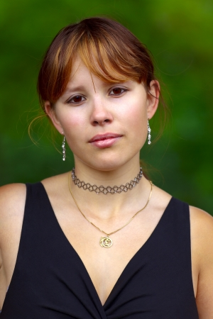 saarlouis: Portrait of a young woman  on a green background, outdoor in a small city Saarlouis. Saarland  Germany Stock Photo