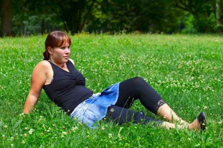 saarlouis: A young woman sits on a green meadow in the sun, outdoor in a small city Saarlouis. Saarland  Germany