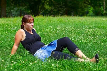 saarlouis: Una mujer joven se sienta en un prado verde en el sol, al aire libre en una peque�a ciudad Saarlouis. Saarland  Alemania