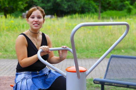 saarlouis: A young woman sitting on sport device and laughs in the pause between sport exercises. Outdoor in park in city Saarlouis, Saarland  Germany.