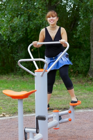 A young woman sitting on sport device and laughs in the pause between sport exercises. Outdoor in park in city Saarlouis, Saarland / Germany. Stock Photo - 14722529