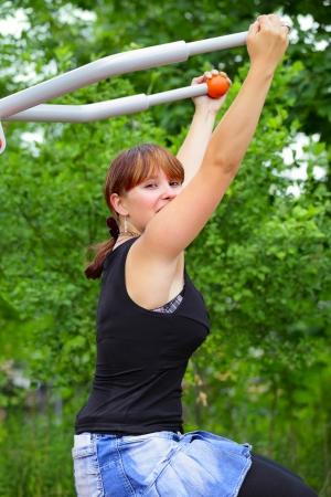 saarlouis: Una mujer joven sentada en el dispositivo de deporte y se r�e en la pausa entre ejercicios deportivos. Al aire libre en el parque en la ciudad de Saarlouis, Saarland  Alemania.