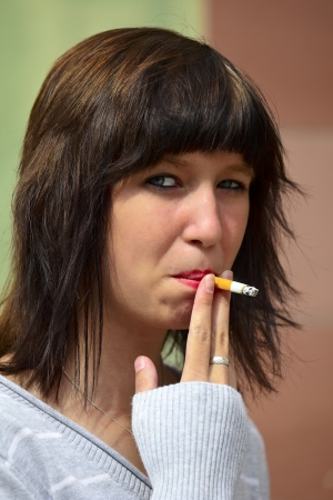 Young woman smokes a cigarette, outdoor in a small city Dillingen  Saarland  Germany photo