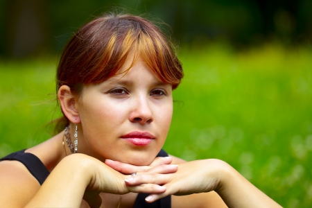 saarlouis: Portrait of a young woman sits on a green meadow in the sun, outdoor in a small city Saarlouis. Saarland  Germany