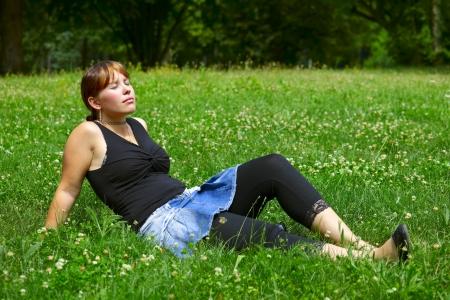 saarlouis: Una mujer joven se sienta en un prado verde en el sol, al aire libre en una peque�a ciudad Saarlouis Saarland Alemania