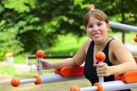 A young woman sitting on sport device and laughs in the pause between sport exercises. Outdoor in park in city Saarlouis, Saarland  Germany.