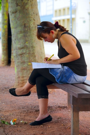 A young woman looking at documents and making notes, sitting on a bench, outdoors in a small city Saarlouis  Saarland  Germany