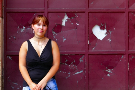 Portrait of a young woman in background red painted window with broken glass, outdoor in a small city Saarlouis  Saarland  Germany. photo