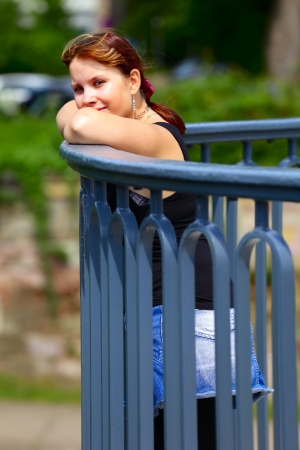 saarlouis: A young woman stands on a bridge railing, in background green blur leaves, outdoor in a small city Saarlouis  Saarland  Germany.