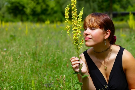 saarlouis: A young woman sits on a green meadow in the sun and smells of a wild flower, outdoor in park in a small city Saarlouis, Saarland  Germany