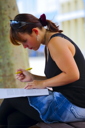 saarlouis: A young woman looking at documents and making notes, sitting on a bench, outdoors in a small city Saarlouis   Saarland   Germany Stock Photo