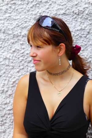 Portrait of a young woman in background a white wall, outdoor in a small city Saarlouis   Germany photo