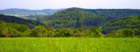 Landscape with a forests and hillocks, at the front village Honzrath in the distance village Dueppenweiler, evening, spring, SaarlandGermany, panoramic Stock Photo