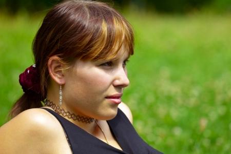 saarlouis: Retrato de una mujer joven se sienta en un prado verde en el sol, al aire libre en una peque�a ciudad Saarlouis. Saarland  Alemania