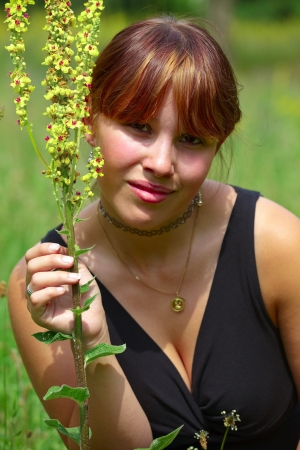 A young woman sits on a green meadow in the sun and smells of a wild flower photo