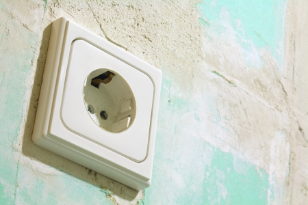 Close up of a electric socket, located on a green plasterboard Stock Photo - 16128770