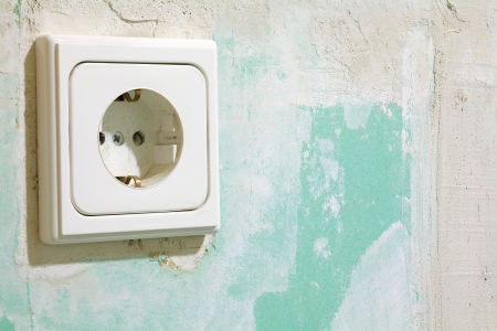 Close up of a electric socket, located on a green plasterboard photo