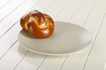 bread roll: Bread roll on ceramic plate, white wooden background.