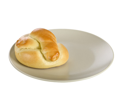 focus stacking: Bread roll on ceramic plate, isolated on white background.