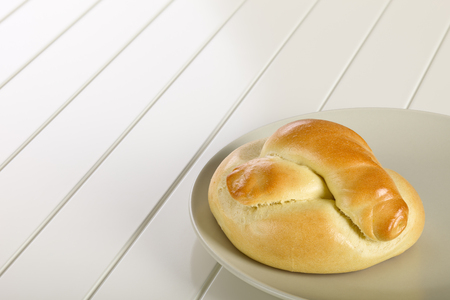 Bread roll on ceramic plate, white wooden background.