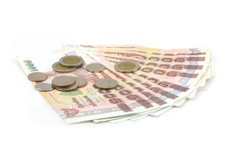 1000 タイお札と白い背景の上のタイの硬貨。