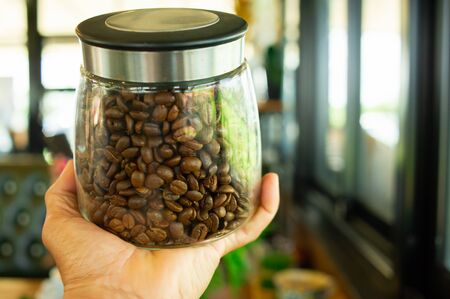 A hand holding a jar of roasted coffee beans