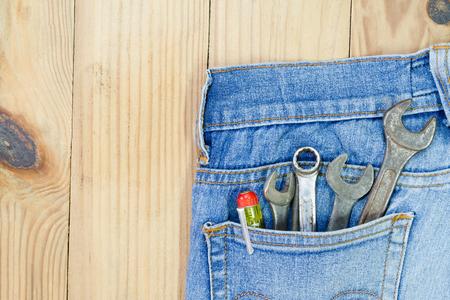 Handwerkzeuge setzen in der Jeanstasche auf dem Holztisch.