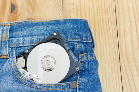 putting in: hard disk storage transport by putting in a jeans pocket on a wooden table