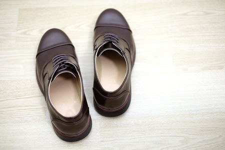 Pair of brown cut shoe on wood floor